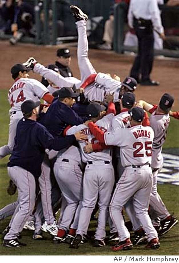 Boston Red Sox Pokey Reese jumps on top of his teammates after the Red Sox defeated the St. Louis Caridnals 3-0 in Game 4 to win the World Series at Busch Stadium in St. Louis, Wednesday, Oct. 27, 2004. (AP Photo/Mark Humphrey) Photo: MARK HUMPHREY