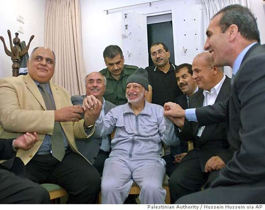 In this picture released by the Palestinian authority Palestinian leader Yasser Arafat, centre, holds hands with unidentified Tunisian, Jordaninan and Egyptian doctors at his compound Thursday Oct. 28, 2004. (AP Photo/Palestinian Authority, Hussein Hussein) ** ** Photo: HUSSEIN HUSSEIN