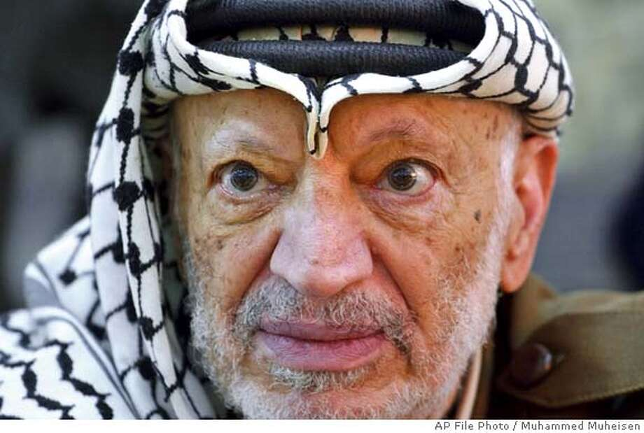 ** FILE ** Palestinian leader Yasser Arafat pauses during an emergency cabinet session, at his compound, in the West Bank town of Ramallah in this Saturday, Oct. 2, 2004 file photo. Late Wednesday, Oct. 27, 2004, Arafat's health deteriorated and his doctors rushed to his room to examine him, an official in Arafat's office said. Soon after, Palestinian Prime Minister Ahmed Qureia and former Prime Minister Mahmoud Abbas were summoned to Arafat's compound, the official said. (AP Photo/Muhammed Muheisen) Photo: MUHAMMED MUHEISEN