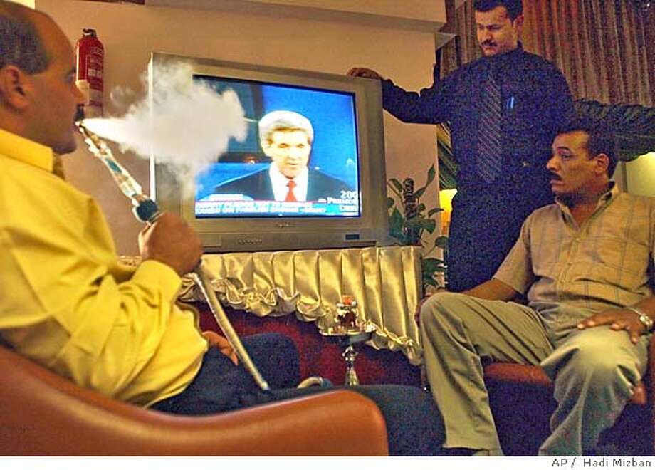 Iraqis follow on a TV screen the televised debate between U.S Democratic presidential nominee John Kerry and U.S. President George W. Bush in a coffee shop in the center of Baghdad, Iraq, Saturday, Oct. 9, 2004. (AP Photo / Hadi Mizban) Ran on: 10-27-2004  In a Baghdad coffee shop, customers watch one of the Bush-Kerry debates earlier this month on television. Photo: HADI MIZBAN