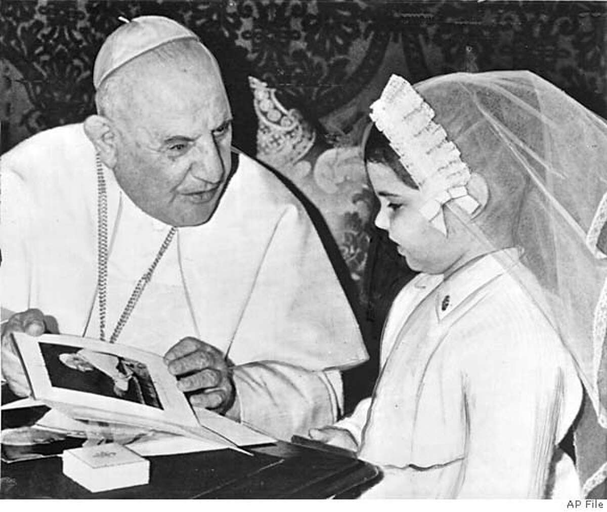 (NY21-April11) Her dream comes true. Pope John XXIII, seated at his desk in the small throne room at the vatican in rome, gives a photo of himself to Catherine hudson, seven-year old leukemia victim of Oklahoma City, OK. Catherine realized her dream of seaaing the Pontiff when she and her mother mrs. Marlene Hudson, were received in a special audience today. Catherine, who doctors say has only a short time to live, had repeatedly asked her mother to please take her to see the pope. Her unemployed mother sold everything they had tp make the trip. (AP wirephotot via radio from Rome) From Chronicle Photo Library April 12, 1960
