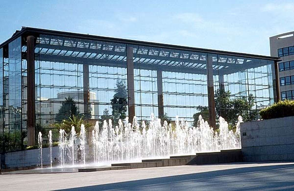 A fountain programmed with leaping water jets by a glass house is viewed from a sloping plaza of stone in Paris' Parc Andre Citroen. Photo by Alice R. Joyce