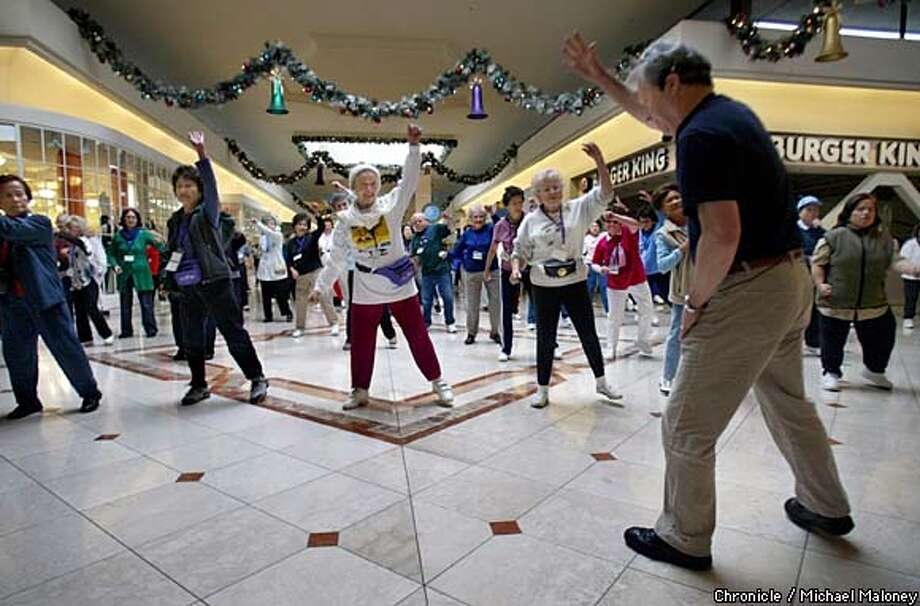 Ray Hanvey, right, leads seniors through a brisk warm-up to music before a walk around Serramonte Mall in Daly City. Chronicle photo by Michael Maloney