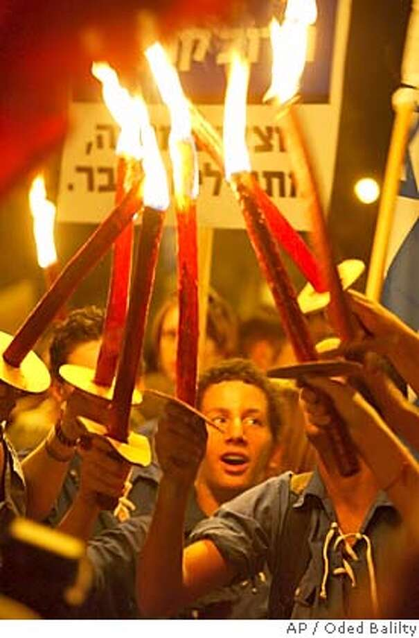 "Israeli pro-peace activists light torches as they march towards the Knesset, Israel's parliament, to show support for the Israeli withdrawal from Gaza Strip, Monday Oct. 25, 2004. Israel's parliament started Monday a historic debate on the Israeli government's proposed ""disengangement plan"" from Gaza. The vote is expected Tuesday evening and Prime Minister Ariel Sharon's aides said he is counting on a comfortable victory. (AP Photo/Oded Balilty) Ran on: 10-26-2004  Peace advocates march toward Israel's Parliament to show support for the Gaza Strip pullout. Photo: ODED BALILTY"