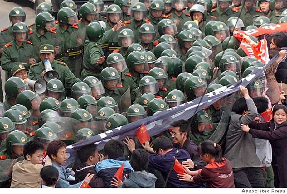 Chinese paramilitary soldiers stand guard as anti-Japanese protesters demonstrate outside of the Japanese consulate in the northeastern Chinese city of Shenyang, Sunday April 17, 2005. China on Sunday rebuffed Japanese demands to apologize for protests that damaged the Japanese Embassy and a consulate, while authorities allowed new demonstrations over Tokyo's wartime history and campaign for a permanent U.N. Security Council seat. (AP Photo) ** ONLINE OUT, CHINA OUT ** Photo: STR