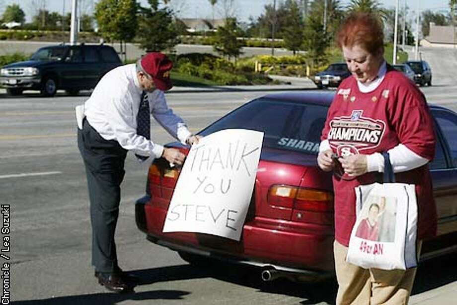 From left: Don of South San Jose and Niner Jan Boehm of Sunnyvale. Don adjusts a sign he attached to his car outside of 49er Headquarters after hearing the news of Steve Mariucci being let out of his contract. PHOTO BY LEA SUZUKI Photo: LEA SUZUKI