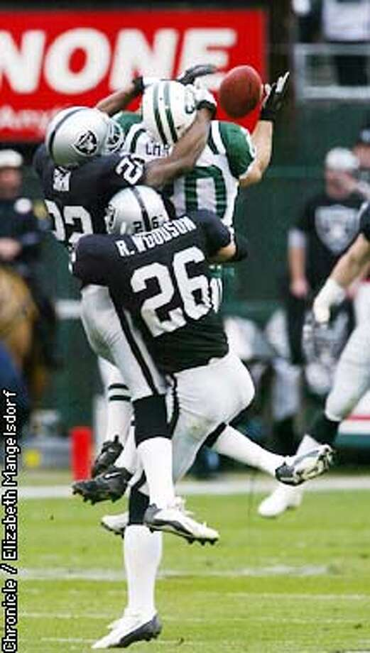 RAIDERS15-C-12JAN03-SP-LM  Raiders #22 Terrence Shaw and #26 Rod Woodson break up pass intended for Jets #80 Wayne Chrebet during the first quarter. The Oakland Raiders play the New York Jets in an AFC playoff game at the Oakland Coliseum January 12, 2003. CHRONICLE PHOTO BY LIZ MANGELSDORF