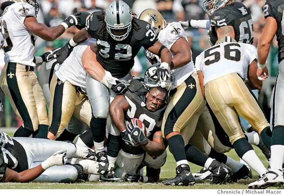 Raider running back 28- Amos Zereoue has his helmet removed by Saints 91-Will smith on a first quarter run.NFL Football. The Oakland Raiders vs. The New Orleans Saints. Network Associates Coliseum.  10/24/04 Oakland, CA Michael Macor / San Francisco Chronicle Photo: Michael Macor