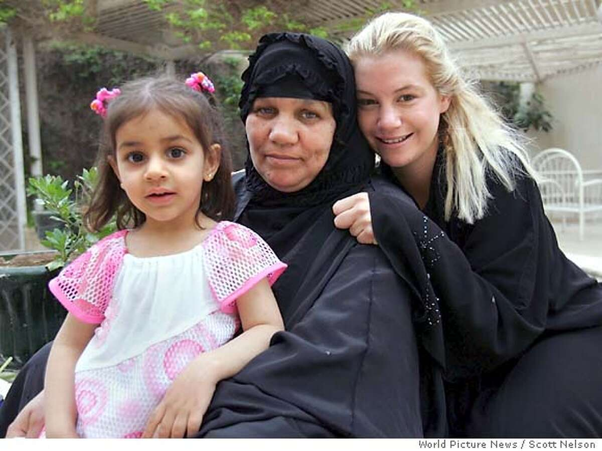 In this photo released by World Picture News on Sunday April 17 2005, American civilian Marla Ruzicka, of the Washington DC-based human rights group Civic Worldwide, poses with an Iraqi family that was helped by her organization in Baghdad, Iraq, Friday, April 15, 2005. Ruzicka was killed by a car bomb attack in Baghdad Saturday, April 16, 2005. (AP Photo / Scott Nelson, World Picture News, ho)
