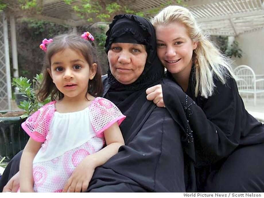 In this photo released by World Picture News on Sunday April 17 2005, American civilian Marla Ruzicka, of the Washington DC-based human rights group Civic Worldwide, poses with an Iraqi family that was helped by her organization in Baghdad, Iraq, Friday, April 15, 2005. Ruzicka was killed by a car bomb attack in Baghdad Saturday, April 16, 2005. (AP Photo / Scott Nelson, World Picture News, ho) Photo: SCOTT NELSON