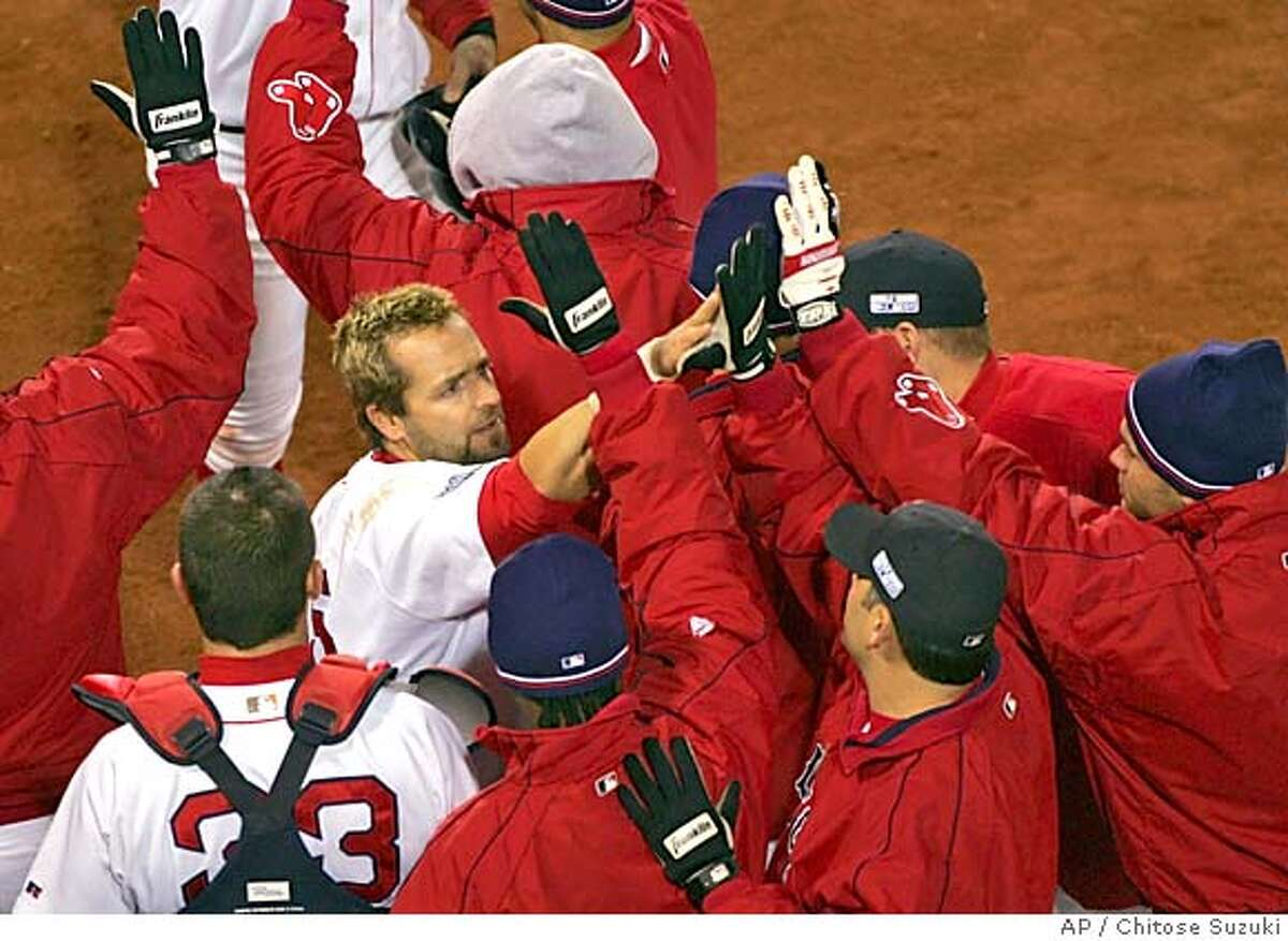 Boston Red Sox Kevin Millar, facing camera, is greeted by teammates after he scored on Mark Bellhorn's fourth inning double against the St. Louis Cardinals in game two of the in Boston, Sunday, Oct. 24, 2004. (AP Photo/Chitose Suzuki)