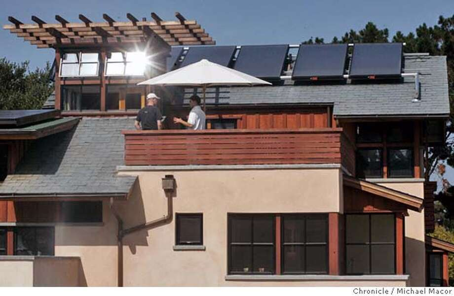 "The D'Souza residence in Belmont features both thermal and photovoltaic, Greg McFetters, right of ""EcoEnergies"", explains the systems to Norm Harris of Menlo Park.San Mateo county hosts a ""Solar Day"" , tours of energy efficient homes through out the area. 10/2/04 Michael Macor / San Francisco Chronicle Photo: Michael Macor"