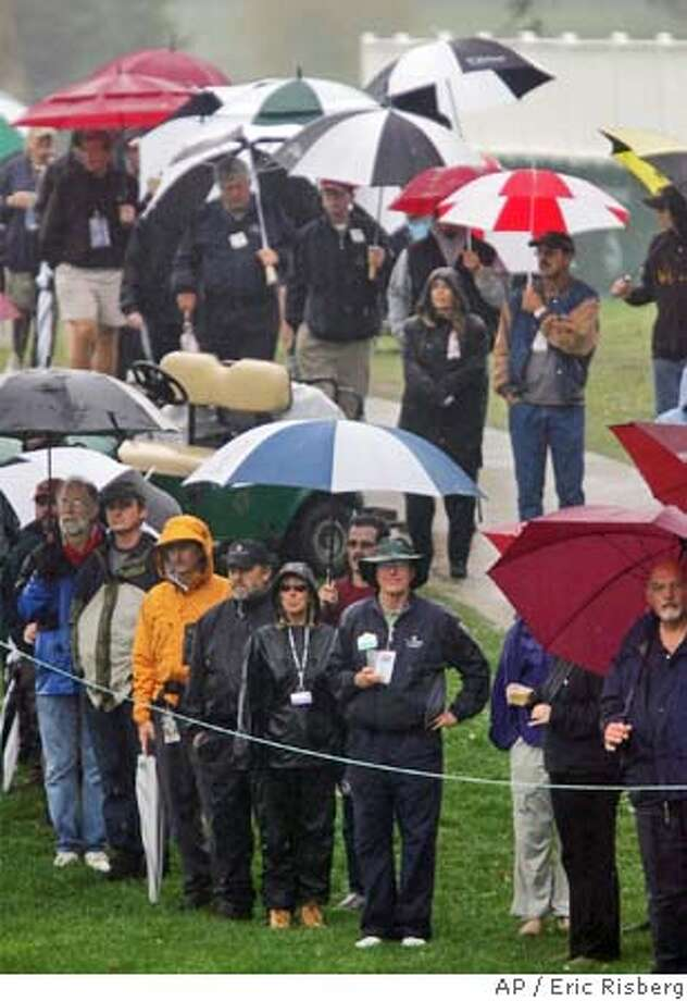 Fans take cover from the rain while watching leader Tom Kite putt on the 18th green of the Sonoma Golf Club during the third round of the Charles Schwab Cup Championship in Sonoma, Calif., Saturday Oct. 23, 2004.(AP Photo/Eric Risberg) Ran on: 10-24-2004  Fans took cover from the steady rain at Sonoma Golf Club while watching tournament leader Tom Kite finish his round on No. 18. Photo: ERIC RISBERG