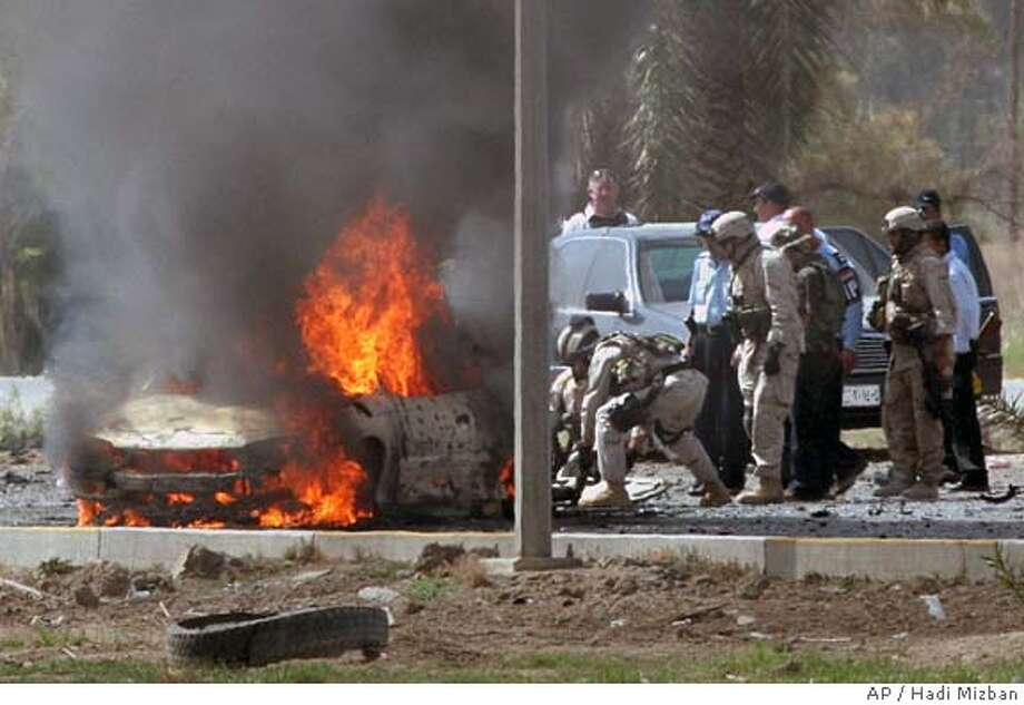 U.S. Army soldiers remove a body from near a burning car after a car bomb attack on the airport road in Baghdad, Iraq Saturday, April 16, 2005. At least four bodies were removed from the scene.(AP Photo/Hadi Mizban) Photo: HADI MIZBAN