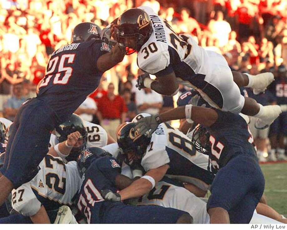 California's J.J. Arrington (30) jumps over the Arizona defense and scores the first touchdown, despite the attempted tackle by Arizona's Kirk Johnson (25) during the first quarter at Arizona Stadium in Tucson, Ariz. on Saturday, Oct. 23, 2004. Arrington (AP Photo/Wily Low) Ran on: 10-24-2004  J.J. Arrington goes over the Arizona defense from the 1-yard line, giving Cal an early 7-0 lead. Arrington finished with 140 yards and the one score on 24 carries. Photo: WILY LOW