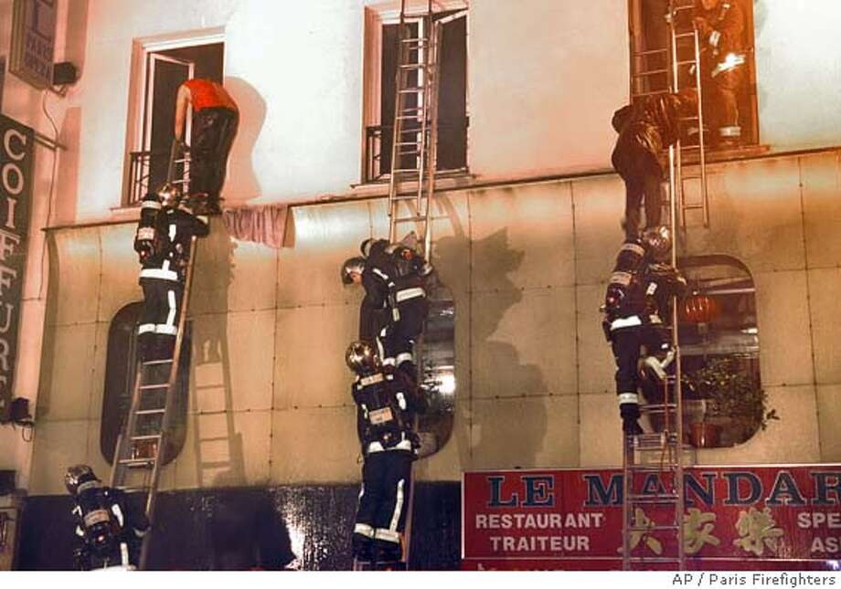 This picture released by the Paris Firefighters shows members of a fire squad evacuating guests from the Paris-Opera Hotel in Paris, Friday, April 15, 2005. At least 20 died and more than 50 were injured after a pre dawn fire swept through the hotel used by city hall to house needy African families. (AP Photo/Paris Firefighters)