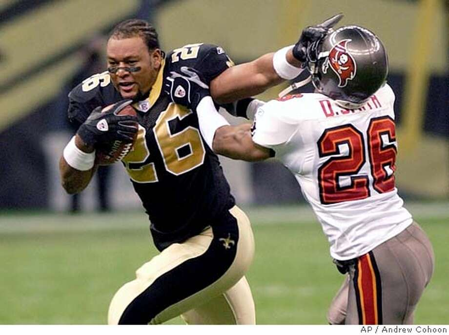 New Orleans Saints running back Deuce McAllister (26) tries to elude Tampa Bay Buccaneers defensive back Dwight Smith (26) in first half, Sunday Dec. 7, 2003 in the Louisiana Superdome. McAllister kept going even after he lost his helmet. (AP Photo/Andrew Cohoon) Deuce McAllister tries to avoid Dwight Smith after losing his helmet on a first-half run. Deuce McAllister tries to avoid Dwight Smith after losing his helmet on a first-half run. CAT Sports#Sports#Chronicle#10/23/2004#ALL#5star##0421519044 Photo: ANDREW COHOON
