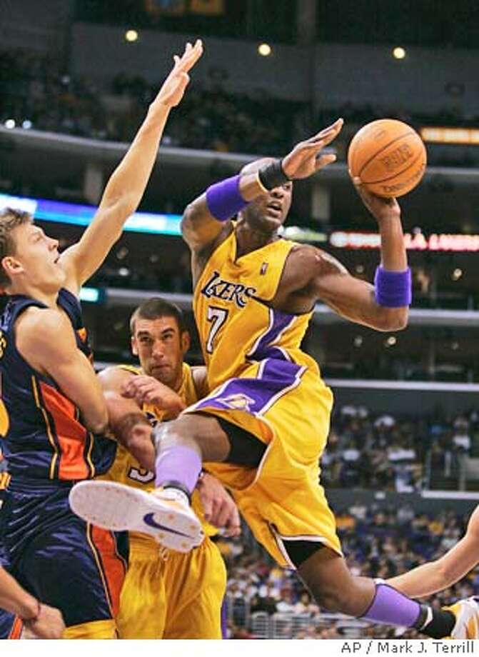 Los Angeles Lakers' Lamar Odom passes the ball as Golden State Warriors' Andris Biedrins guards and Lakers teammate Chris Mihm gets caught between during the first half of pre-season play, Thursday, Oct. 21, 2004, in Los Angeles. (AP Photo/Mark J. Terrill) Photo: MARK J. TERRILL