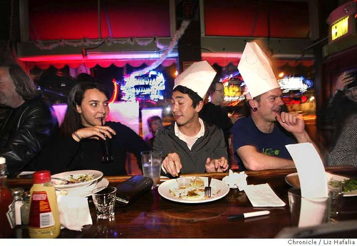 Left to right--Cecilia Trigos has a house salad while her friends Mitsuo Kuroha (cq) and Patrick Parnell have a cheeseburger and fries at the Hotel Utah. Shot in San Francisco on 3/24/05.