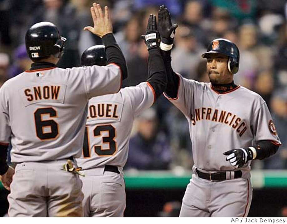San Francisco Giants' Pedro Feliz, right, is congratulated by teammates Omar Vizquel (13) and J.T. Snow after feliz hit a grand slam off Colorado Rockies starting pitcher Jamey Wright during the fourth inning at Coors Field in Denver, Friday, April 15, 2005. (AP Photo/Jack Dempsey) Photo: JACK DEMPSEY