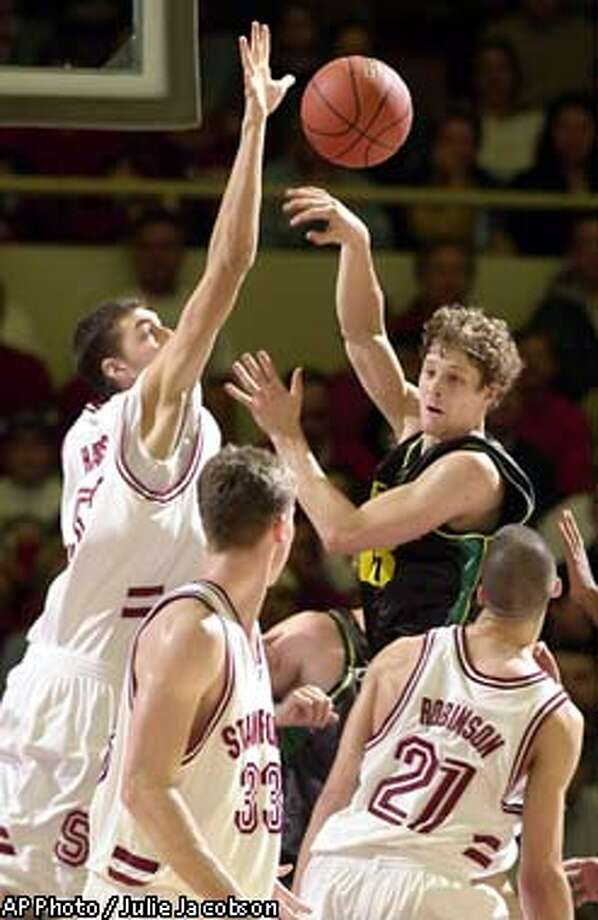 Oregon's Luke Ridnour passes to an open teammate while surrounded by Stanford's Matt Haryasz, left, Matt Lottich, center, and Nick Robinson during the second half Saturday, Jan. 11, 2003, in Stanford, Calif. Ridnour led the Ducks with 19 points in Oregon's 57-81 loss, becoming the 24th Oregon player with 1,000 points; he now has 1,014. (AP Photo/Julie Jacobson) Photo: JULIE JACOBSON
