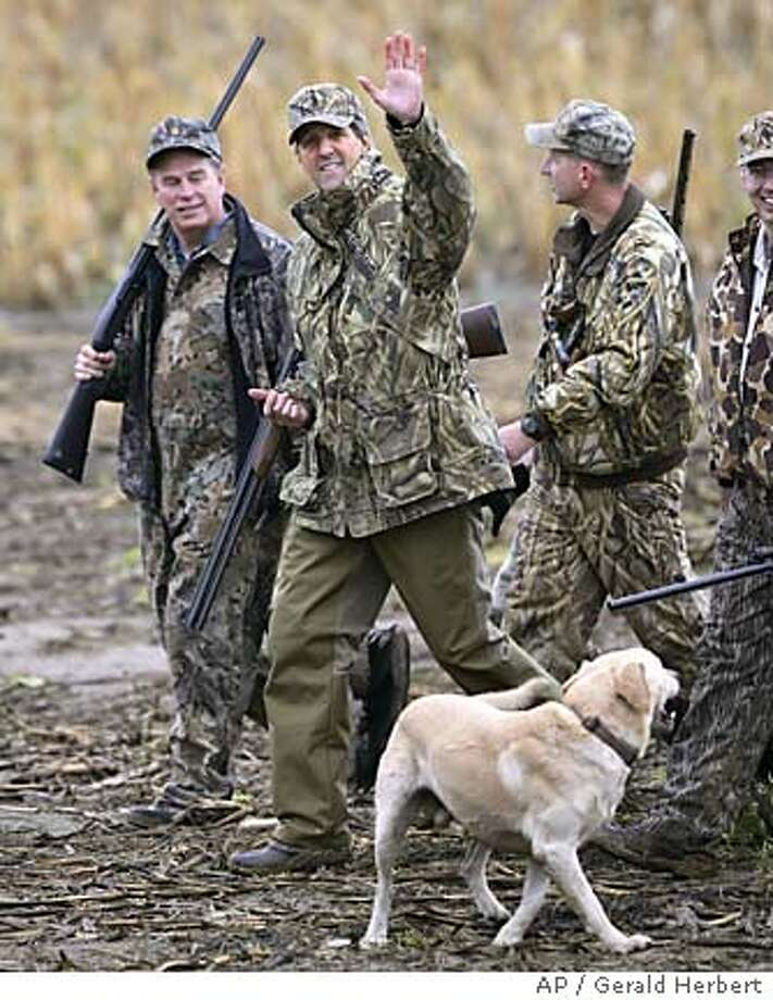 Democratic Presidential candidate Sen. John , D-Mass., second from left, waves as he returns from a goose hunting trip with Rep. Ted Strickland, D-Ohio, left, Bob Bellino, a board member for the local Ducks Unlimited, second right, and Neal Brady, assistant park manager of Indian Lake State Park in western Ohio, right, in Poland, Ohio, Thursday, Oct. 21, 2004. With them is a yellow Labrador named Woody. (AP Photo/Gerald Herbert) Photo: GERALD HERBERT