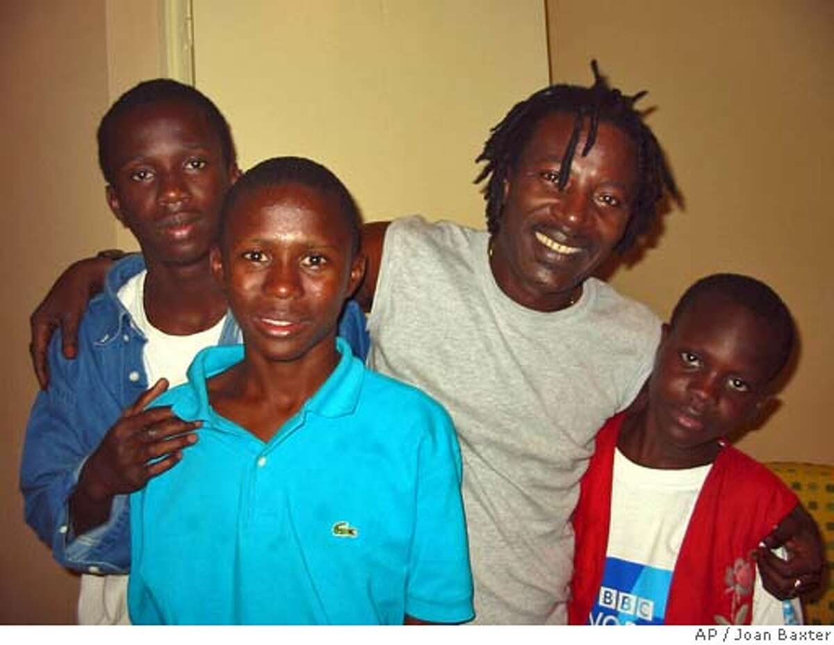 ** ADVANCE FOR WEEKENDEDITIONS, JAN. 9-12 **African reggae star Alpha Blondy, second from right, stands for a photo with some young fans in Bamako, Mali, Dec. 30, 2002. For years Blondy's songs have warned of the dangers of tribalism, racism, inequality and injustice in his country, but he says his voice is not as loud as the deadly music of machine guns. (AP Photo/Joan Baxter) CAT HFR 01-09-03. ADVANCE FOR WEEKEND EDITIONS, JAN. 9-12 Datebook#Datebook#Chronicle#10/23/2004#ALL#Advance##421184428