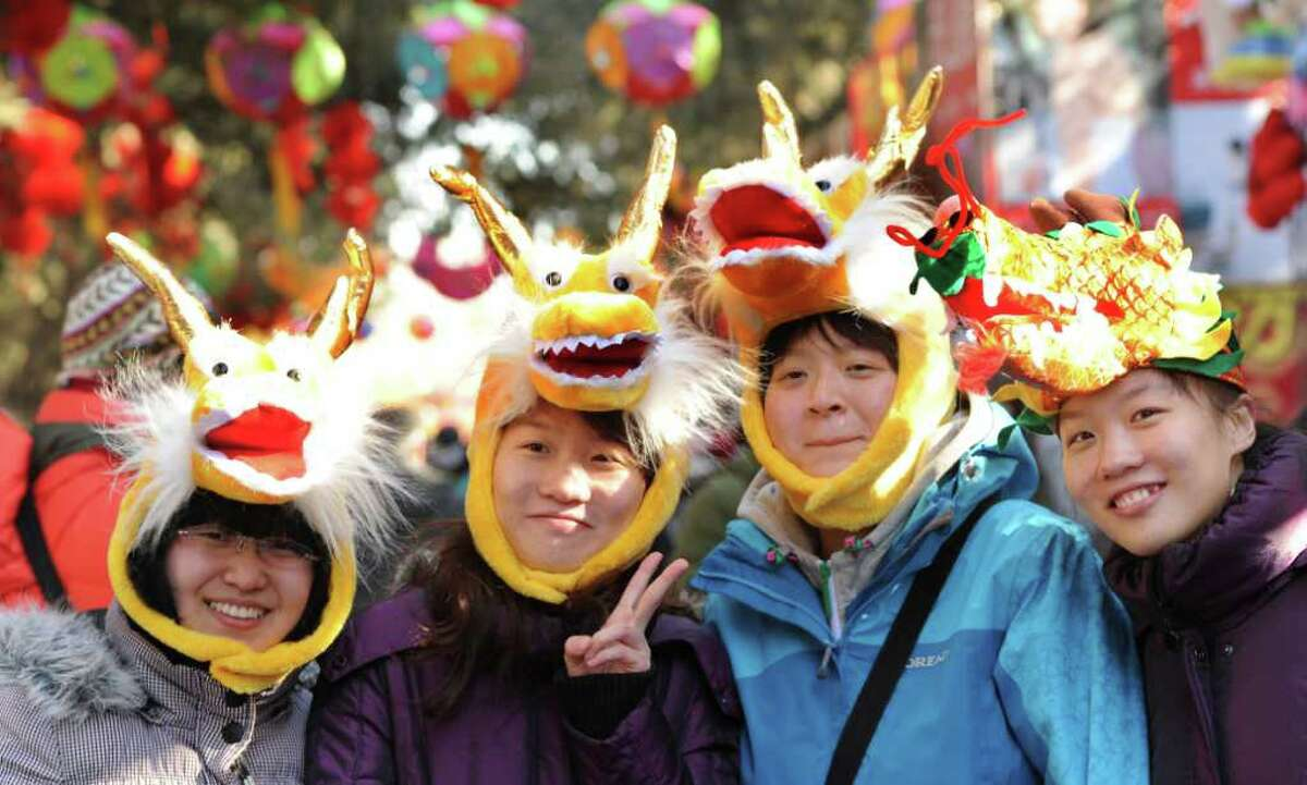 Chinese women wear dragon hats as they tour the Ditan Temple Fair, which is one of the highliights of the Lunar New Year in Beijing on January 22, 2012. China is welcoming the year of the dragon, a symbol considered to be particularly auspicious because it is the only mythical creature among the dozen animals that represent each year in the Chinese cosmic cycle.