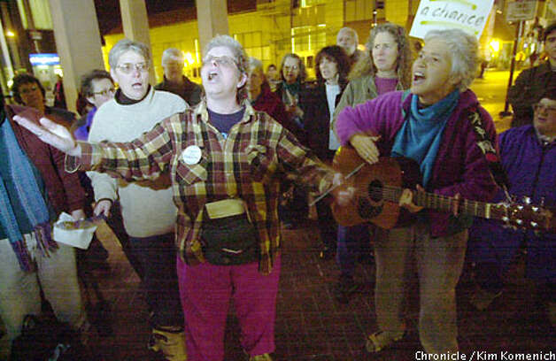 Singing for Peace, whose members are opposed to a U.S. war in Iraq, serenade passers-by during a vigil at the Berkeley BART station on Shattuck Avenue. Chronicle photo by Kim Komenich