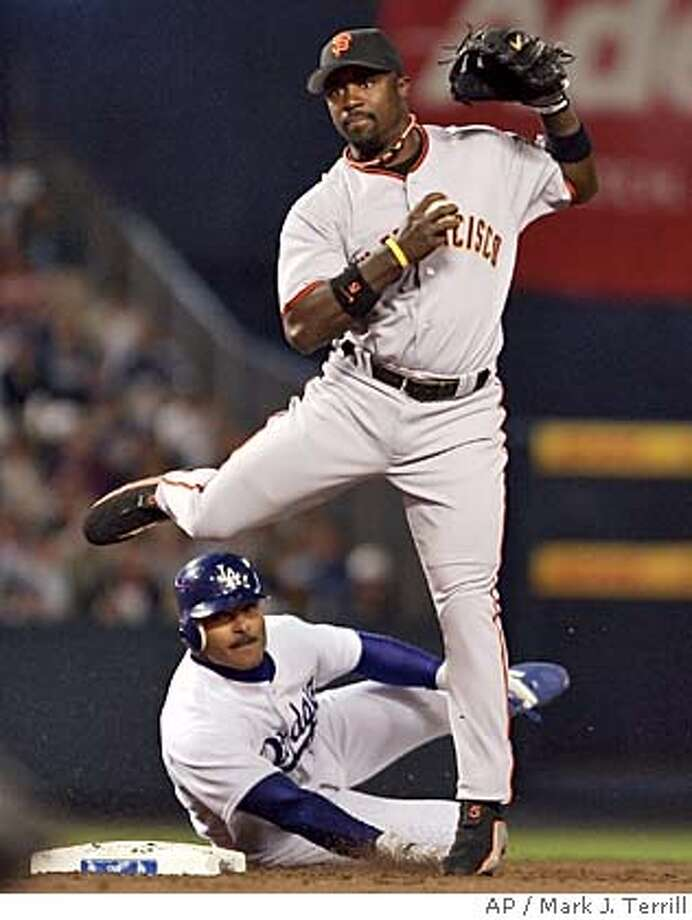 Los Angeles Dodgers' Jose Valentin, below, breaks up a double play attempt by San Francisco Giants' Ray Durham at second during the second inning, Wednesday night, April 13, 2005, in Los Angeles. (AP Photo/Mark J. Terrill) Photo: MARK J. TERRILL