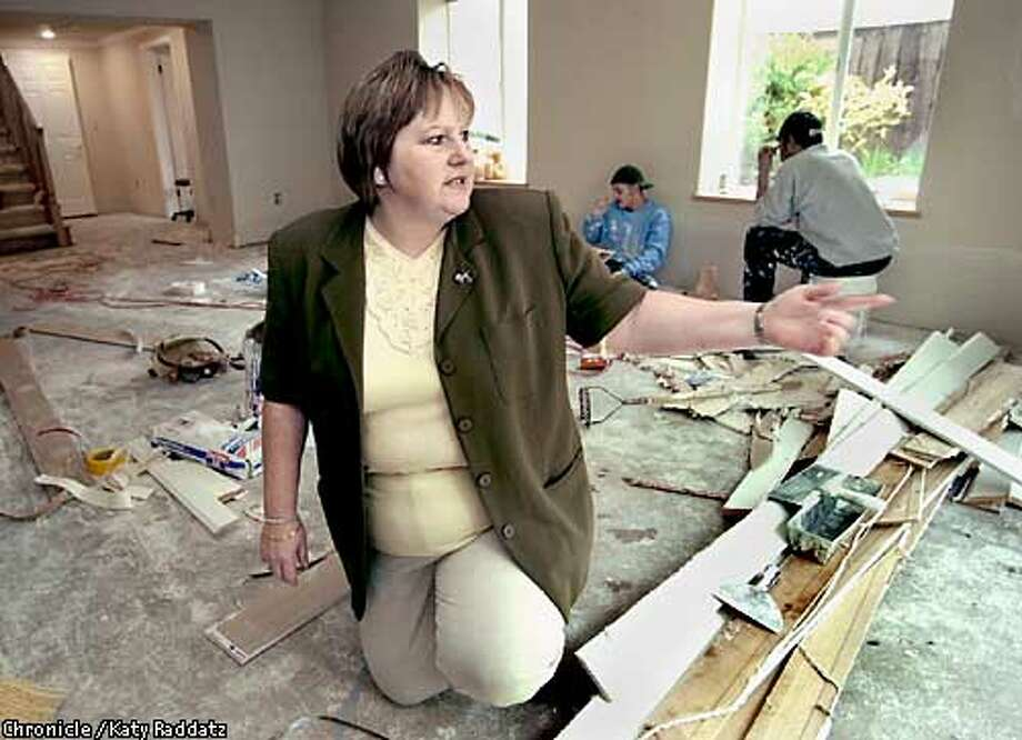 PHOTO BY KATY RADDATZ--THE CHRONICLE  Liz Parker's house in Burlingame was flooded after a six hour power outage left her sump pump impotent. She and her husband Kevin will testify to PG&E at a town hall meeting soon. SHOWN: Liz in her basement, where she explains the extent of the damage, while her hard working repair crew takes a lunch break. Photo: KATY RADDATZ