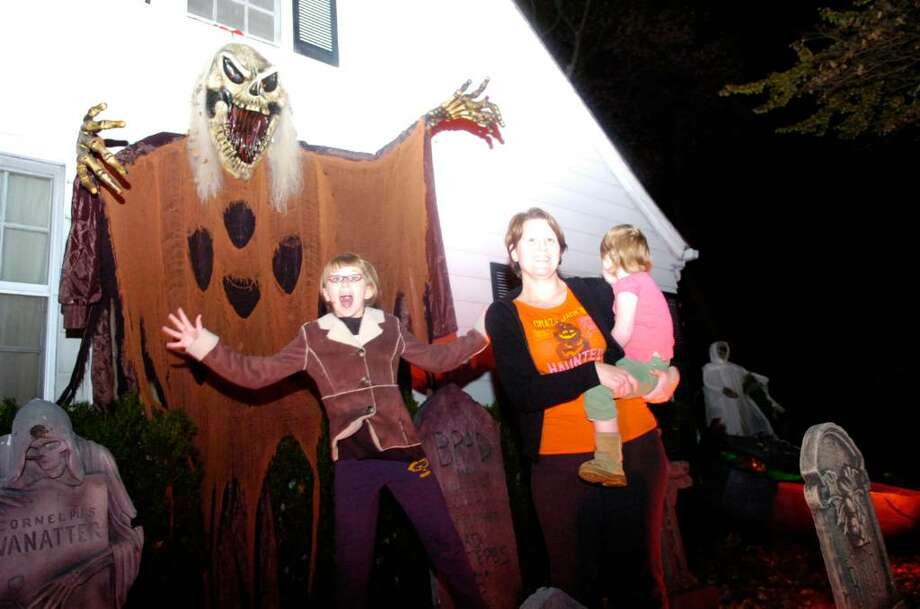 """Queen of Halloween"" Karen Hasterok and daughters Quinn Hasterok, 2, and Alexandra Buss, 10, left, stalk the night at their Old Greenwich home on Wendel Place Thursday evening, Oct, 29, 2009. The Hasterok Halloween fever has spread and they now do traditional decorating battle with neighbors led by Andrew Buss (unrrelated to Alexandra.) The verdict is still out on who won this year's contest. Photo: Keelin Daly / Greenwich Time"