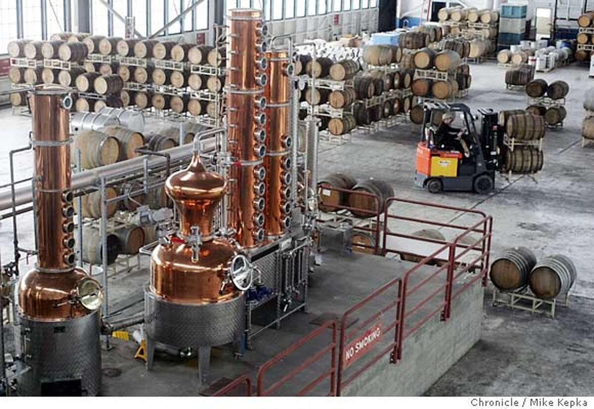 The copper still is the anchor for St George Spirits in the new aiplane hanger home home in Alameda. St. George Spirts master distiller, Jorge Rupf recently opened a tasting room at the new distillery in Alameda. Mike Kepka / The Chronicle