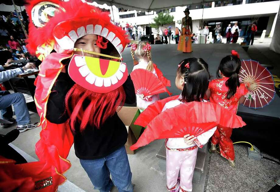Eric Zheng, 8, peers out from his lion head costume before performing with the Alamo Chinese Language School dance group at the 2010 Asian Festival at the Institute of Texan Cultures. Photo: KIN MAN HUI, San Antonio Express-News / San Antonio Express-News