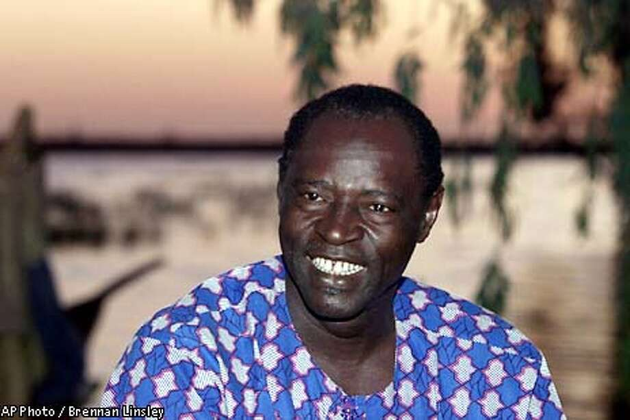 """ADVANCE FOR WEEKEND EDITIONS, THURSDAY MARCH 8 - 12 -- Ali Farka Toure smiles on the banks of the Niger River Nov. 21, 2000 in his hometown of Niafunke, about 110 miles northeast of Mopti, Mali. The guitarist, whose Grammy-winning 1994 album """"Talking Timbuktu"""" stayed at the top of Billboard's world music chart for nearly eight months, is spending more time in Niafunke, playing for his friends, his family, and himself. ( AP Photo / Brennan Linsley ) Photo: BRENNAN LINSLEY"""