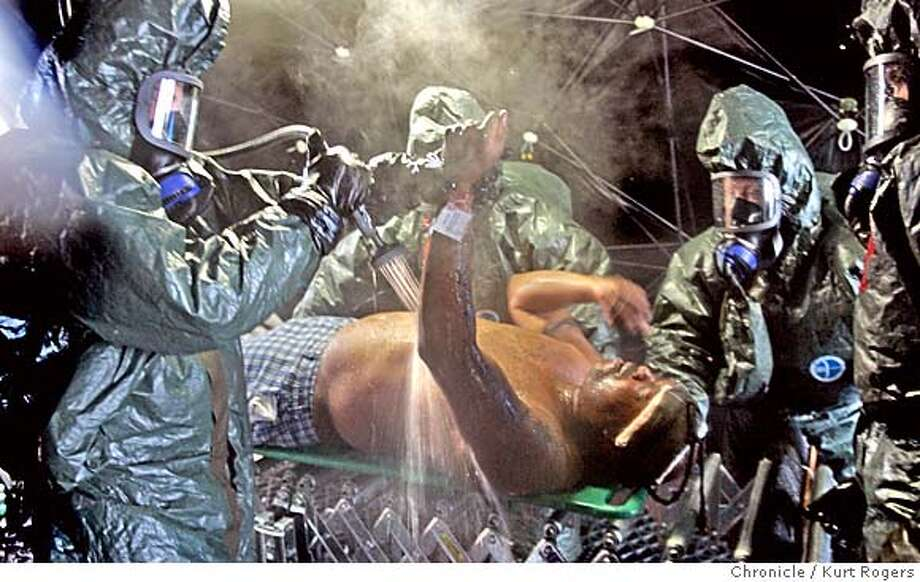 This victim is being treated by Christopher Hilebrane from Chico, Pitricia Allison from Yreka and Levi Menuonca of Chico. in the Decontamination tent they are spraying him with hot water.  Members of the California National Guard held a WMD attack drill. At Camp Roberts near Paso Robles. The drill used the scenario that the Network Associates Coliseum in Oakland was the target of an attack. The Guard were taking victims of the attack and treating them as if they were victims as it they had been exposed to radiation .  ROBERTS_0777_kr.JPG 10/19/04 in Camp Roberts,CA.  KURT ROGERS/THE CHRONICLE MANDATORY CREDIT FOR PHOTOG AND SF CHRONICLE/ -MAGS OUT Metro#Metro#Chronicle#10/20/2004#ALL#5star#a3#0422421968 Photo: KURT ROGERS