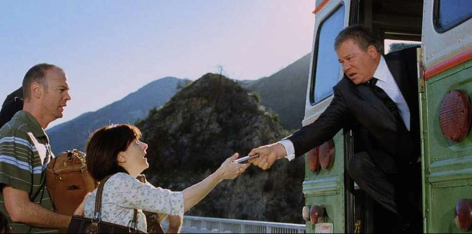 In this image released by priceline.com, William Shatner is shown in a scene from a Priceline.com commercial. In a new commercial, William Shatner's Priceline pitchman, the Negotiator, makes a costly sacrifice for a deal. In a new 30-second TV spot set to begin airing next week, the Negotiator rescues panicked vacationers from a bus teetering on a bridge's railing. (AP Photo/priceline.com) Photo: Anonymous, ASSOCIATED PRESS / AP2012