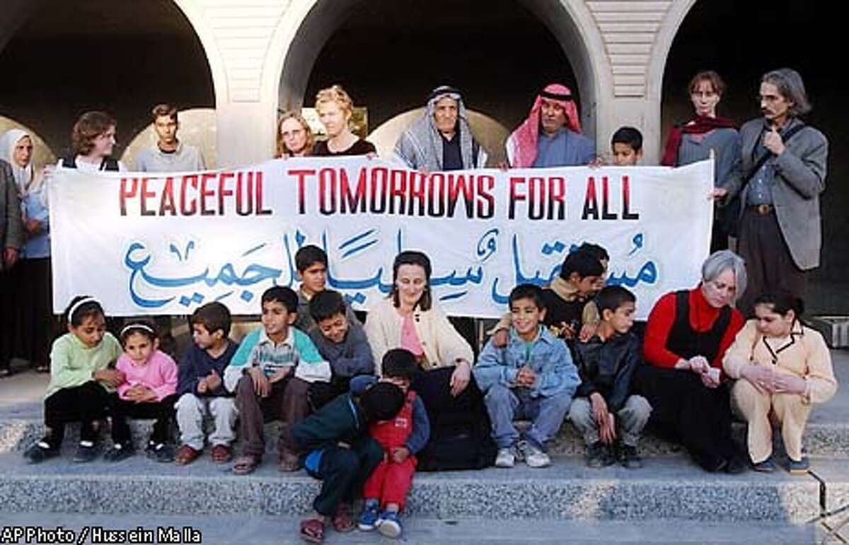 Members of the Peaceful Tomorrows group who had relative killed in the September 11 attacks, seen with other US peace activists and Iraqi people, hold a peace banner at al-Amariya shelter in Baghdad, Iraq, on Wednesday, Jan. 8, 2003. The Peaceful Tomorrows members met to grieve with Iraqis whose relatives were killed 10-years ago when allied warplanes struck the bomb shelter.(AP Photo / Hussein Malla)