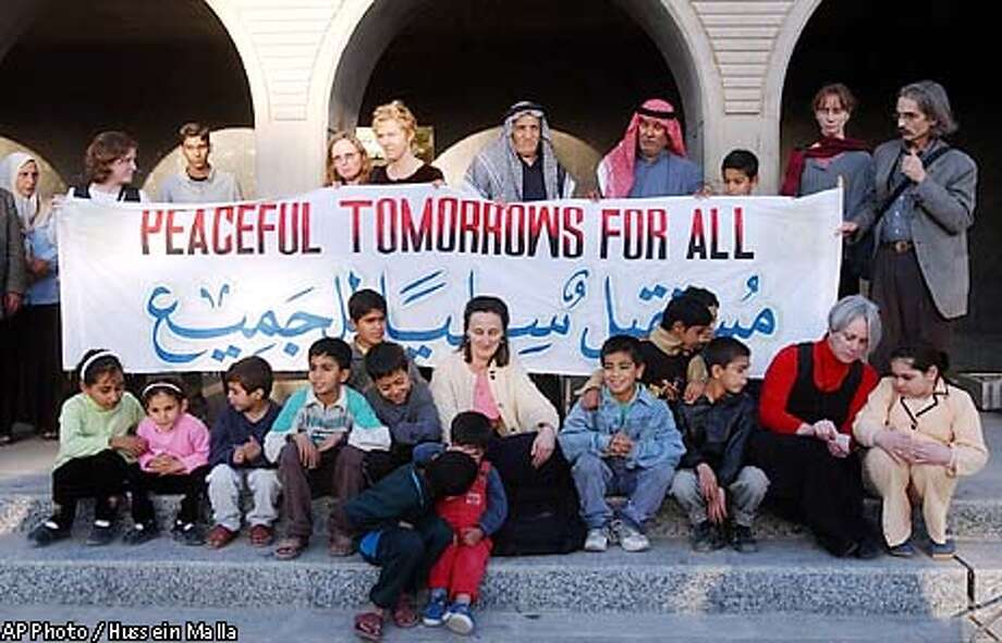 Members of the Peaceful Tomorrows group who had relative killed in the September 11 attacks, seen with other US peace activists and Iraqi people, hold a peace banner at al-Amariya shelter in Baghdad, Iraq, on Wednesday, Jan. 8, 2003. The Peaceful Tomorrows members met to grieve with Iraqis whose relatives were killed 10-years ago when allied warplanes struck the bomb shelter.(AP Photo / Hussein Malla) Photo: HUSSEIN MALLA