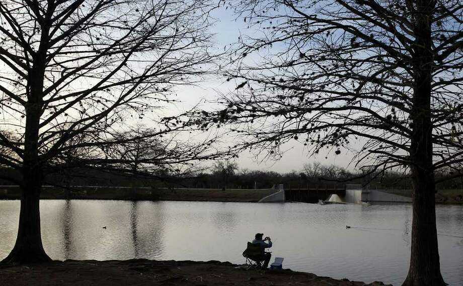 Billy Marek takes advantages of a near perfect morning to fish at South Side Lions Park on Jan. 23, 2012. He also took out his camera to take a photograph of the scene.  A change of weather is expected Tuesday and Wednesday with thunderstorms in the forecast. Photo: Jerry Lara, San Antonio Express-News / © 2012 San Antonio Express-News