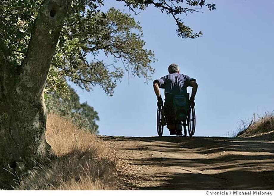 """WHEELCHAIR_11_MJM.jpg  Bob Coomber crests a hill at one of his favorite hikes - the trails of Morgan Territory Park near Livermore.  Bob Coomber is wildland enthusiast. He spends most of his free time in the east bay parks or Sierra, exploring the wide open spaces. He is also a paraplegic, and his excursions are all conducted via an all-terrain wheelchair. Coomber is an activist for making more of the wilderness wheelchair accessible, but only, he says, in a """"gentle"""" way. He feels many areas are inappropriate for improved trails, and he wants only minimal grading for those areas where they make sense. Folks in wheelchairs, he feels, have to be up to the challenge, conditioning themselves to handle the wilderness. Photo by Michael Maloney / San Francisco Chronicle MANDATORY CREDIT FOR PHOTOG AND SF CHRONICLE/ -MAGS OUT Metro#Metro#Chronicle#10/18/2004#ALL#5star##0422403386 Photo: Michael Maloney"""
