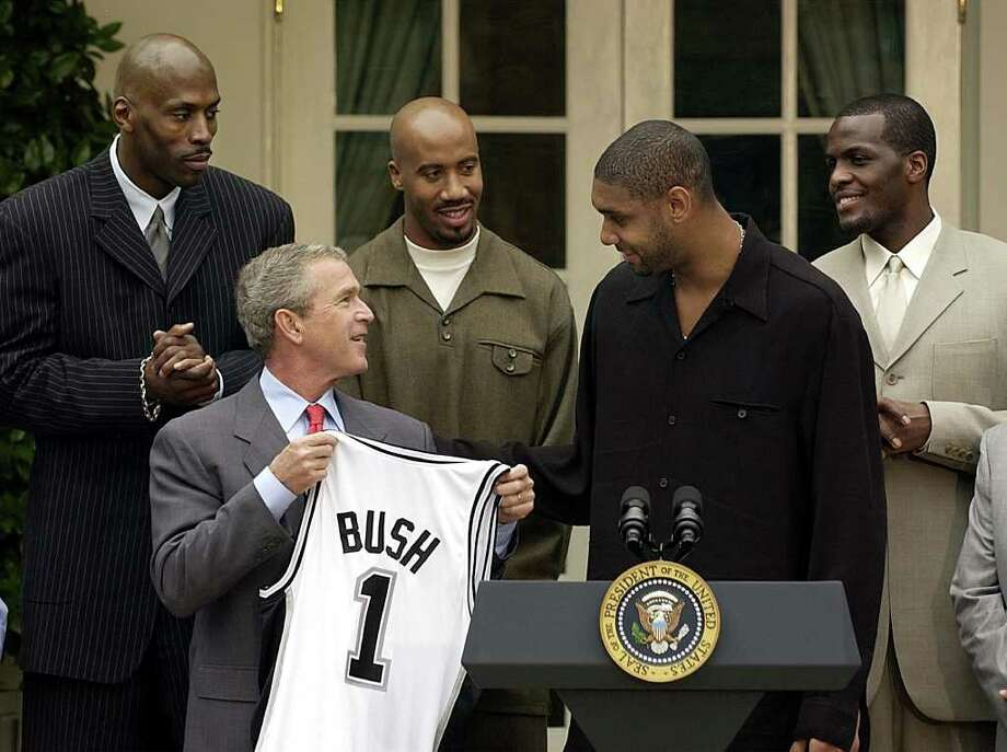 President Bush holds a basketball jersey presented to him by the NBA Champion San Antonio Spurs during a ceremony in the Rose Garden of the White House Tuesday, Oct. 14, 2003. With him, left to right, are Kevin Willis, Bruce Bowen, Tim Duncan and Malik Rose. (AP Photo/Gerald Herbert) Photo: GERALD HERBERT, Express-News / AP