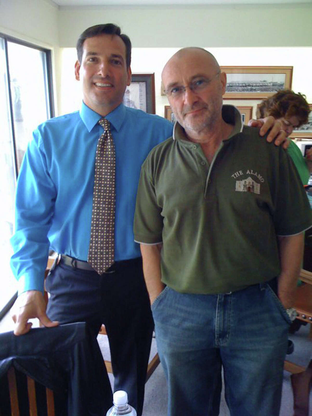 The Alamo's director of marketing and public relations Tony Caridi poses with singer and Alamo enthusiast Phil Collins in 2010. Caridi has been fired by the Daughters of the Republic of Texas for alleged inappropriate use of work computers and other employee resources. Caridi, who was the face of the Alamo during controversies that led to a new law providing state oversight of the Texas shrine, was fired on Friday and has retained a lawyer. COURTESY PHOTO
