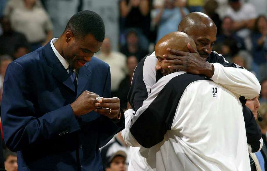 Former Spur David Robinson looks Tuesday Night Oct. 28, 2003 in the SBC Center at his new NBA championship ring while Spurs Kevin Willis and Bruce Bowen celebrate getting their rings.        (WILLIAM LUTHER/STAFF) Photo: WILLIAM LUTHER, Express-News / SAN ANTONIO EXPRESS-NEWS