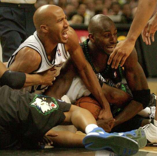 Minnesota Timberwolves' Kevin Garnett, right, battles San Antonio Spurs' Bruce Bowen for a loose bal