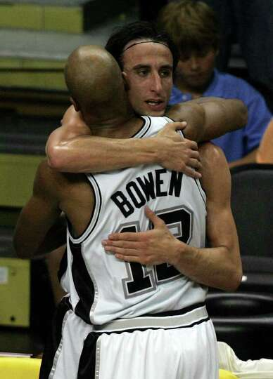 Spurs' Manu Ginobili hugs teammate Bruce Bowen in the closing moments of the fourth quarter of game