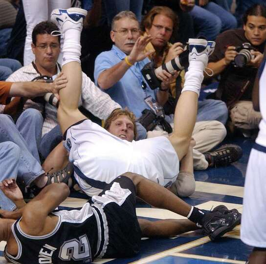 Spurs' Bruce Bowen and Mavericks' Dirk Nowitzki fall into courtside photographers during first quart