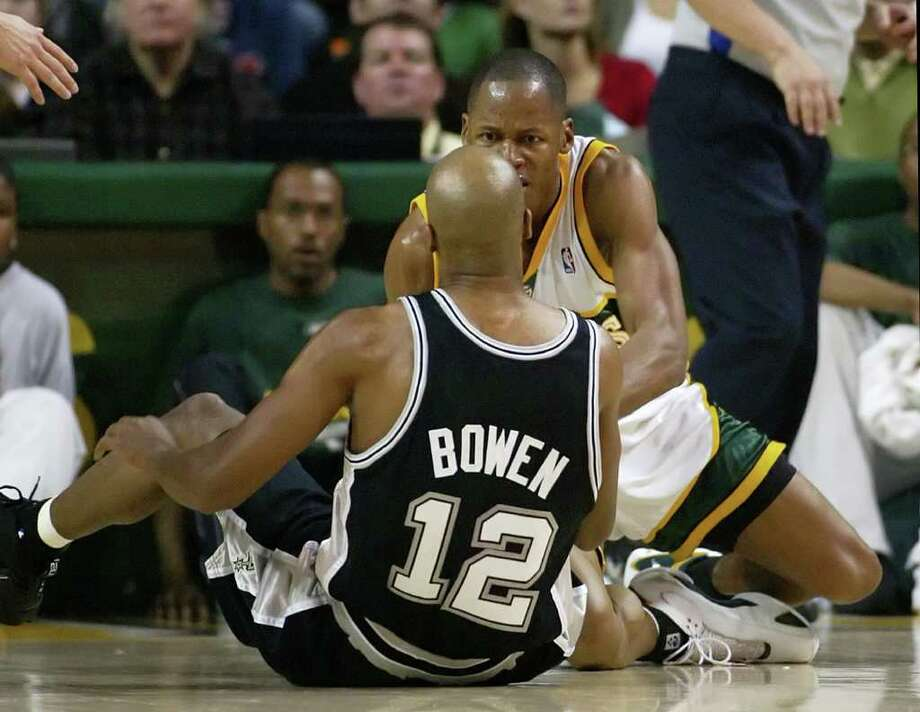 Seattle SuperSonics' Ray Allen, back, reacts to San Antonio Spurs' Bruce Bowen during the second quarter of an NBA basketball game in Seattle, Sunday, March 26, 2006. Allen was first called for an offensive foul and Bowen responded by apparently kicking Allen. Bowen was given a technical, and Allen had to be restrained. (AP Photo/John Froschauer) Photo: JOHN FROSCHAUER, Express-News / AP