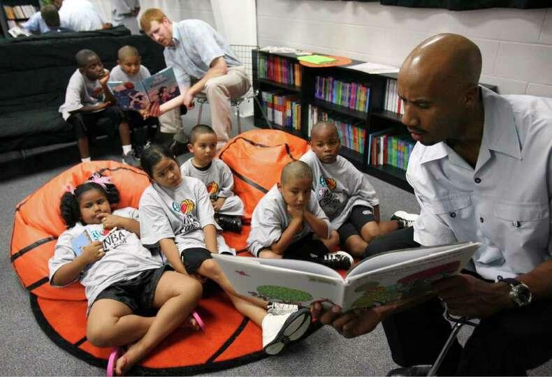 Spurs' Matt Bonner (rear) and teammate Bruce Bowen read to children Friday June 8, 2007 during the d