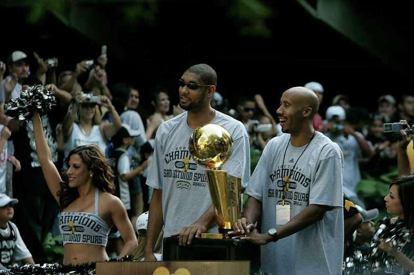 Tim Duncan, left, and Bruce Bowen, right, pass cheering fans on the parade route during the Spurs NB